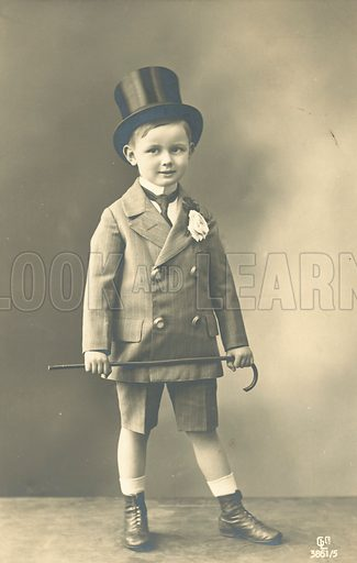 Boy in double-breasted suit, wearing a top hat and holding a cane. Postcard, early 20th century.