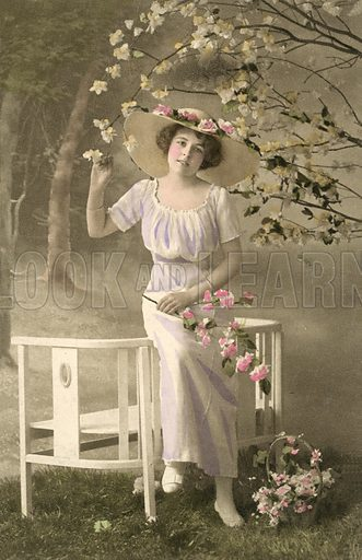 Pretty girl in loose dress picking blossom. Postcard, early 20th century.