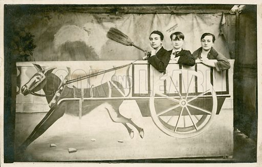 Three people riding a photo prop cart.  Postcard, early 20th century.