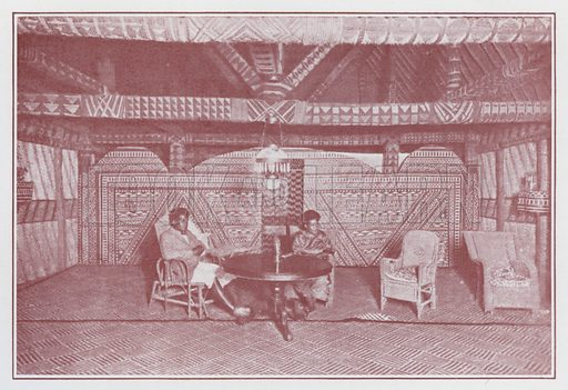 """Interior of a Chief's House, Bau. The cross-beams, ties, and wall-plates are covered with sinnet, plaited in various designs and colours. The screen on the back wall is of native """"masi,"""" a cloth made from the bark of the """"Paper-mulberry,"""" and the design is printed with native dyes. The floor is covered with mats plaited from the leaves of a species of pandanus. The table in the centre is that on which the Dead of Cession was signed. Illustration for The Colony of Fiji, 1874–1924 (S Bach, Government Printer, 1924). Note: Copyright of photos is credited to Government of Fiji."""