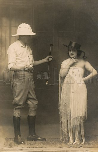 Portrait of a man dressed for riding and a woman wearing a hat and a dress. Postcard, early 20th century.