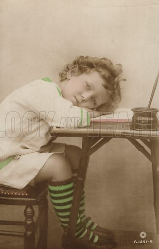 Portrait of a sleepy young child at a writing desk. Postcard, early 20th century.