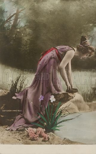 Woman looking into a pond. Postcard, early 20th century.