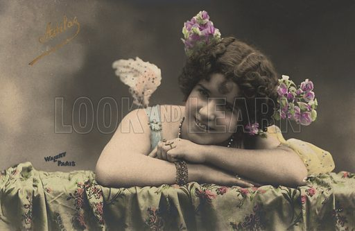 Portrait of a woman with flowers in her hair, possibly a French dancer, singer or actress at around the turn of the 20th century. Postcard, early 20th century.