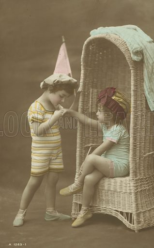 Young boy kissing the hand of a little girl. Postcard, early 20th century.