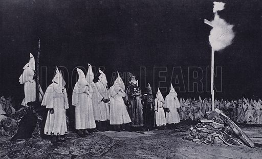 Imperial Wizard and Grand Cyclops at the centre of a group of chiefs opposite the burning cross at a Ku Klux Klan assembly after an initiation ceremony, Georgia, USA . Illustration from The Illustrated London News, 3 February, 1923.