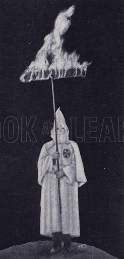 Member of the Ku Klux Klan carrying a burning cross, USA. Illustration from The Illustrated London News, 3 February, 1923.