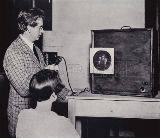 John L Baird giving an early demonstration of television. The image of a person holding two dolls is seen on the little screen. 'Seeing by wireless' has made big strides since this photograph was taken. Illustration for Master Minds of Modern Science by T C Bridges and H Hessell Tiltman (new edn, Harrap, 1934).  Photo credit: none.