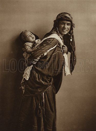 Tunisian Bedouin woman with child. Illustration for Picturesque North Africa (Jarrolds, c 1925).  First published by Ernst Wasmuth, Berlin, 1925.  Gravure-printed. Photo credit: Lehnert and Landrock, Cairo.