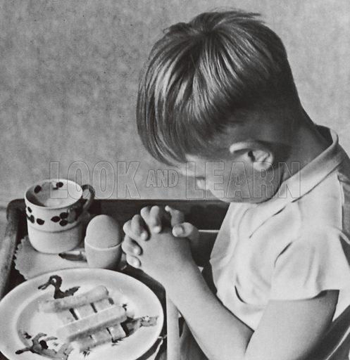 Little boy saying grace before breakfast