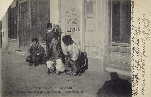 Korean children employed as porters, Vladivostok, Russia, early 20th Century. A poster advertising a performance of Carmen is on the wall behind the children.