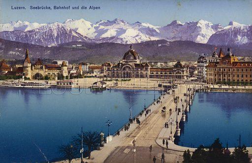 Lucerne – bridge, train station and the Alps. Postcard, circa early twentieth century.