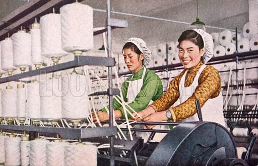 Smiling textile workers spinning cotton in a factory in communist China, 1953.