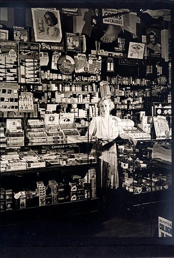 Woman shopkeeper in a tobbaconist's.