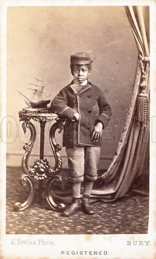 Full-length portrait of a black boy, leaning his right elbow on a pedastal table with a model ship on it. Photograph by E Eccles, Bury.