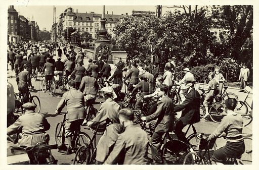 Massed bicyclists crossing a bridge in London. Postcard, early 20th century.