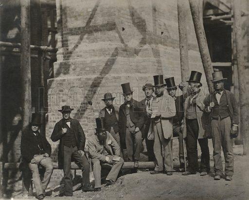 Group of men posing beside a bridge under construction or repair, 19th Century.