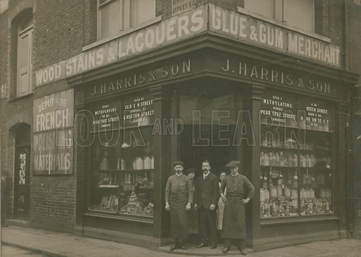 A shopkeeper and his staff standing in the entrance of his shop, J Harris & Son, a hardware shop, London.