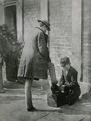 A young shoeblack shining a man's shoes on the street