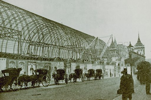 General view of the Royal Aquarium, Westminster, London, with a row of horse-drawn carriages parked outside.