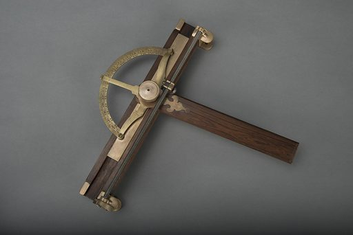 This instrument has a wooden handle attached by a large brass thumbscrew to a brass protractor that is divided to single degrees and numbered by tens in both directions from 10 to 170. The protractor is screwed to a rectangular brass piece that slides in a groove in a rectangular wooden guide-piece. The guide-piece has brass clamps and thumbscrews for affixing the instrument on a table. The protractor is also attached by a split nut to a metal screw shaft that runs the width of the instrument. A thumb rest and gear on the left clamp rotates the screw shaft. Date: 1870s. Record ID: nmah_690213.