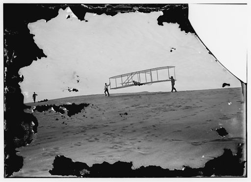 Start of a glide; Wilbur in motion at left holding one end of glider (rebuilt with single vertical rudder), Orville lying prone in machine, and Dan Tate at right; Kitty Hawk, North Carolina. Date 1902 Oct. 10.