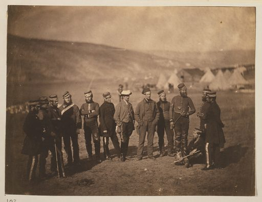 "Major Burton & officers of the 5th Dragoon Guards. Adolphus Burton and twelve officers at camp; the men are wearing several uniform styles. ""Major Burton, Dr Cattell, Llieutenant Montgomery, Lieutenant Hampton, Lieutenant Ferguson, Major Inglis, Captain Godman, (Major Burton,) Captain Halford, Lieutenant Burnand, and Quartermaster Bewley, Officers of the 5th Dragoon Guards (enumerated from the left)."" Source: Exhibition of the Photographic Pictures taken in the Crimea, by Roger Fenton, Esq. … at the Gallery, corner of St James"