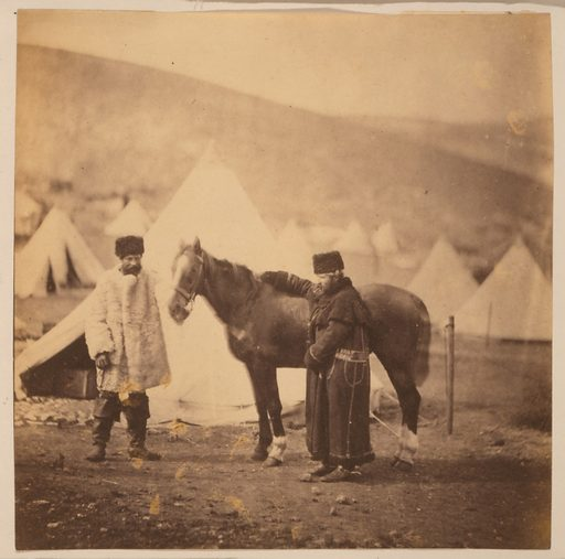 Colonel Lowe, ie Low 4th Light Dragoons & servant in winter dress. Colonel Low, full-length portrait, facing left, standing beside horse and wearing winter coat and hat; another man is standing in front of the horse and facing the camera. Bell tents in the background. Date 1855.