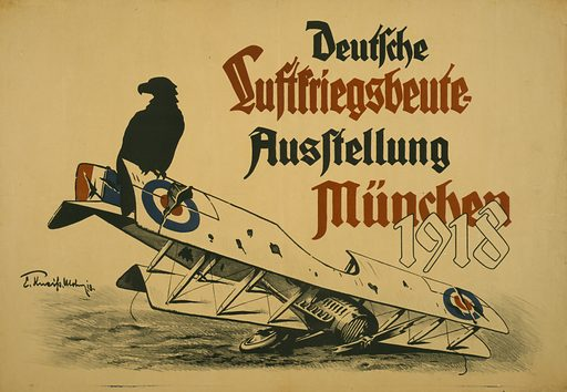Deutsche Luftskriegsbeute Ausstellung München 1918. Poster shows a black eagle sitting on the wing of a downed British biplane. Text announces an exhibition in Munich of the spoils of the air war. Date 1918.
