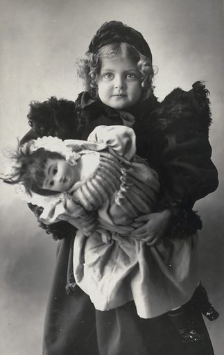 J36. Photograph shows a young girl dressed in a fur-trimmed coat and hat, carrying her doll