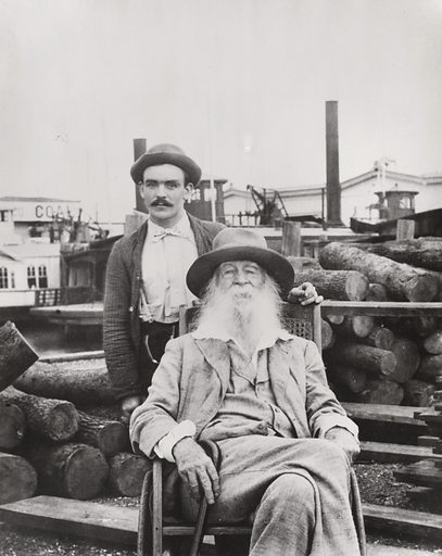 Walt Whitman, three-quarter length portrait, seated, facing front, with his nurse Warren Fritzenger, standing, and a pile of logs behind him, on the wharf, probably near his Mickle Street house in Camden. Date 1890, copied later.