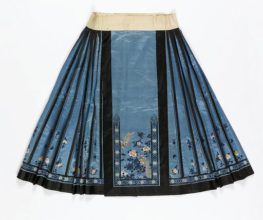 Blue silk satin skirt embroidered in colored silks with a design of flowers and birds; trimmed with black satin bands and black silk braid. Waistband of white linen lined with pink silk woven with a fret pattern. The skirt is made in two parts designed to wrap around the body, with straight panels in the front and back and pleated sections at each side. Made in: China. Date: 1800s. Record ID: chndm_1941-31-31.