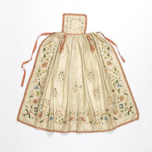 White silk taffeta apron with a small bib and full gathered skirt, embroidered with a deep border and small sprays in field of vines, flowers and grape clusters in many colors. Trimmed with a pink silk galloon; belt and ties of pink silk ribbon. Made in: France. Date: 1800s. Record ID: chndm_1949-119-1.