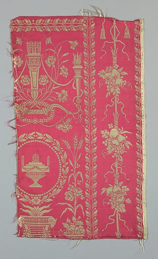Directoire-style design in white on raspberry-colored satin ground shows various archeological and natural objects in rectangular compartments of varying sizes outlined by bands of laurel leaves and berries, in a symmetrical layout. Pattern includes an altar flanked by tall vases of flowers and wheat, quiver with arrows on horizontal bow and flanked by cornflowers, urn in wreath of laurel, chinoiserie pagoda and palms; and in smaller framing compartments, butterflies, bird and nest, winged serpents drinking from fountain, and fruit garland. Pale pink and green striped satin selvages. Made in: France. Date: 1790s. Record ID: chndm_1952-127-19-a_c.