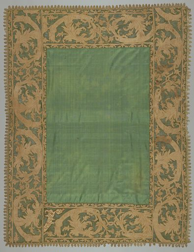 Oblong table cover of dark green silk bordered with green net in an appliqued design of foliage in reversed scrolls that terminate in lilies. Applique is natural colored linen embroidered in dark yellow silk. Edged with natural colored needle lace. Made in: Italy. Date: 1700s. Record ID: chndm_1952-162-55.