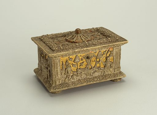 A gilt wood and metal casket depicting a scene. Oblong box with projecting base and cover, four flattened ball feet, and rosette and round knob-sides and cover gilt and punch-marked. Moulded and carved reliefs representing on front the Calydonian Boar Hunt; on back, the Judgment of Paris; on sides, the Baptism of the Samarians by Philip and Judith. On cover, two pairs of winged genii holding wreaths. Pilasters on corners, acanthus moulding on base and lower part of cover. Moulding with oak leaves on cover, which is hinged to body with simple eyelet hinges. Part of snap lock on front--corresponding part on cover missing. Made in: Northern Italy. Date: 1500s. Record ID: chndm_1953-101-1.