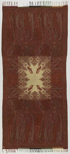 Paisley shawl with deep borders in shades of red, orange, blue, and white. Shawl ends have a row of tall paisleys with an inner border of small paisley motifs. White center field has small paisleys, scrolling bands and floral clusters. Made in: Nimes, France. Date: 1840s. Record ID: chndm_1967-85-25.