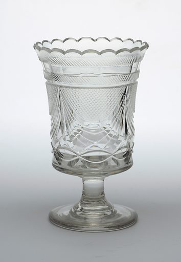 Tall straight sides slightly flared at scalloped top rim, flat bottom, tall spool stem on flat circular base; sides cut with large swags with small diamonds above and a row of losenges below, under rim has a row of facets with blazes on each side. Date: 1800s. Record ID: chndm_1986-61-146.