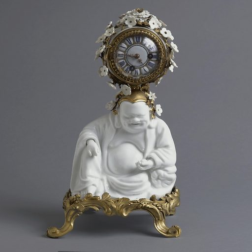 A white porcelain figure of Budai on a gilt bronze four legged base; circular clock in bronze housing covered in small white porcelain flowers on top of figure's head. Made in: France. Date: 1740s. Record ID: chndm_1967-48-123.