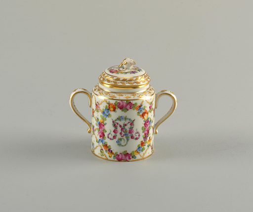 Cylindrical body and domed lid with gilded flower finial. Two handles. Diamond lattice pattern with flowers at crossings. Floral monogram. Date: 1900s. Record ID: chndm_1992-5-62-a_b.