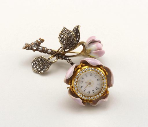 Chatelaine watch forms the core of a wild rose, the stem and foliage of which are composed of enameled gold, studded with diamonds. Maker: Tiffany & Company, American, established 1853. Made in: New York, New York, USA. Date: 1890s. Record ID: chndm_1979-16-1.