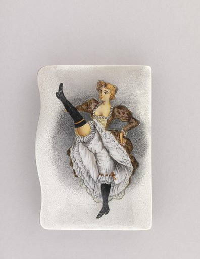 Rectangular, snuff box type container, featuring vertically situated, polychrome enamel image of blond cancan dancer with right leg kicked high. She wears patterned pink dress with low bodice, white petticoats and bloomers, thigh-high black stockings and black shoes. Lid's lip or left edge curved. Lid hinged on right side. Striker on back of same long right side panel. Date: 1900s. Record ID: chndm_1978-146-259.