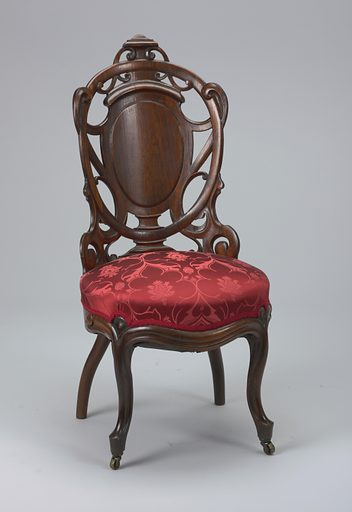 Shaped back, curved in plan, with ovoid escutcheon surrounded by openwork design of laminated wood in scrolls; cabriole legs, the front pair fitted with castors. Upholstered in comtemporaneous machine-woven fancy compound satin. Pressed, steamed, laminated in layers, then glued together at right angles; with an applied crest. Made in: New York, USA. Date: 1860s. Record ID: chndm_1937-4-3.