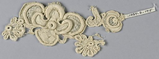 Fragment with a design of a large central flower with flanking buds. Minute superimposed rosettes. Outer petals of large flower in a diamond diaper pattern. Made in: Venice, Italy. Date: 1700s. Record ID: chndm_1897-8-175.