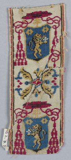Trimming for livery with a design of ecclesiastic's hat over shield showing lion rampant alternating with ornament of conventionalized flowers. In red, blue and yellow on white ground. Made in: Spain. Date: 1800s. Record ID: chndm_1932-3-26.