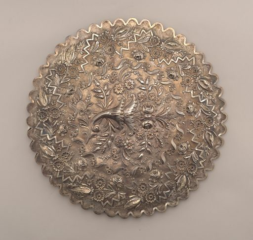 Scalloped circular silver frame engraced with leaves and flowers holding mirror glass. Back repousse with floral wreath, with horn-of-plenty bouquet in center. Made in: Turkey. Date: 1830s. Record ID: chndm_1931-64-12.