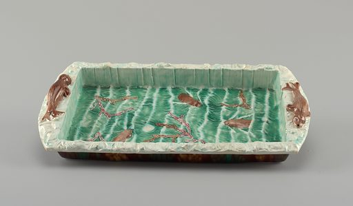 Molded rectangular tray. Straight sides, angled lip, extended at ends to form handles. Reclining seals molded on handles. Interior glazed with three swimming brown animals surrounded by green waves. Made in: Burslem, England. Date: 1870s. Record ID: chndm_1984-105-1.