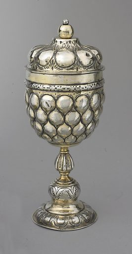 repoussé pineapple pattern on cup(a) and lid (b), with parcel-gilt band at connection, above a lobate stem and foot. Cover finial is gilt silver ball secured to cover by pin with small round silver head. Made in: Nuremberg, Germany. Date: 1610s. Record ID: chndm_1966-2-7-a_b.