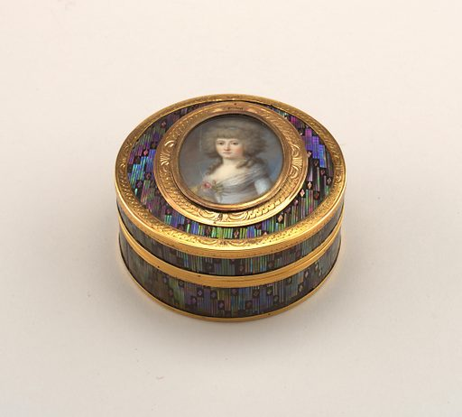 Box, circular, with detachable cover; black lacquer on papier maché inlaid with all-over diaper design in mother-of-pearl with green, blue and purple iridescence; on cover, within gold frame, a hinged oval miniature of a lady in a blue gown, on ivory under glass; a concealed spring releases this and discloses a hidden miniature of a man with powdered hair wearing the blue ribbon of an order and an ermine bordered red robe, painted on ivory, under glass in a very narrow gold frame; border of cover and of main miniature gold engraved with guilloche design; plain molded gold rims; box and cover lined with tortoiseshell. Made in: Paris, France. Date: 1770s. Record ID: chndm_1967-48-13-a_b.
