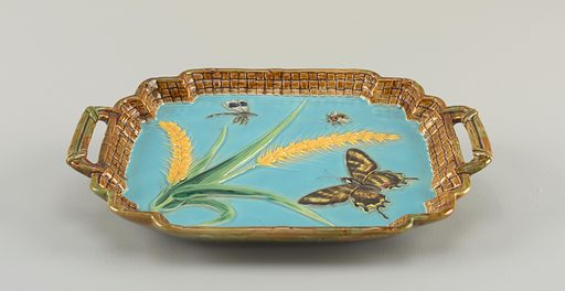 Rectangular tray with lobed upturned edges molded in basket weave pattern, glazed brown and green. Two handles similarly glazed. Center with blue ground and relief decoration of wheat in green and yellow, butterfly and flying insects in polychrome. Underside glazed in highly mottled sponged green, brown and yellow. Made in: England. Date: 1880s. Record ID: chndm_1986-109-12.